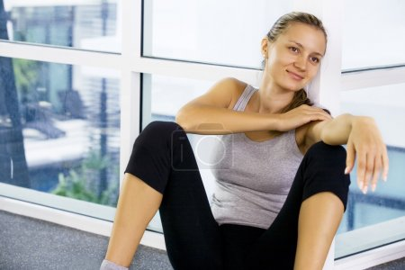 Portrait of young nice woman having rest in gym