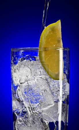 Photo for Close up view of iced tonic glass with lemon on blue back - Royalty Free Image