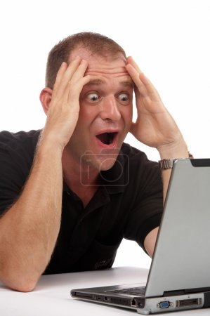 View of a businessman having some exciting news on the screen of his computer