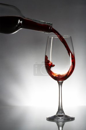 Red wine pouring into glass isolated on gray background