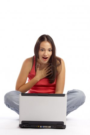 View of young cute emotional brunette sitting behind her laptop