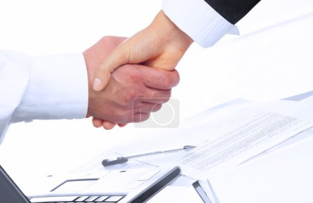 Photo pour Vue de la poignée de main sur papier et ordinateur en arrière-plan - image libre de droit