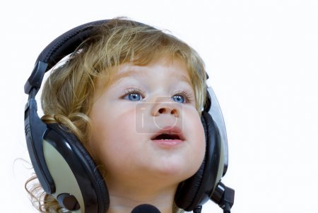 Portrait of young baby listening music via phones