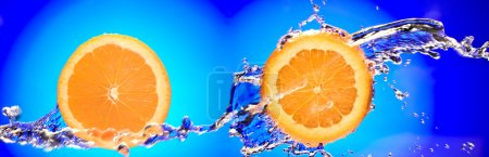Close up view of two sliced orange pieces getting splashed with water