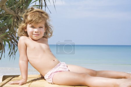 Portrait of nice little girl having fun on the beach