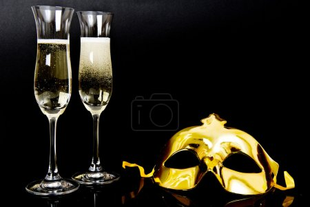 Two glasses of champagne and venetian mask