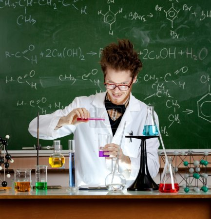 Photo for Mad professor pours some red liquid in beaker while making an experiment in his laboratory - Royalty Free Image