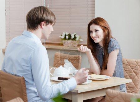 Photo pour Femme parle avec un homme assis à la table à la maison du café - image libre de droit
