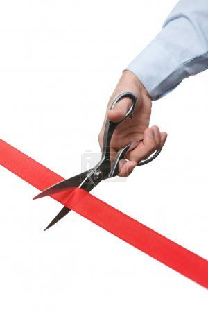 A businessman cutting a red ribbon