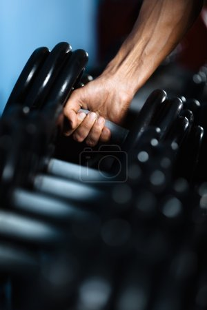 Hand taking out a dumbbell