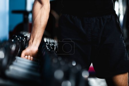 Photo for Hand of a man choosing a dumbbell out of set of black dumbbells - Royalty Free Image