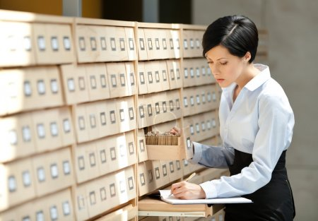 Pretty woman searches something in card catalog
