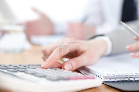 Photo pour Entreprise comptant sur la calculatrice assise à la table. Gros plan sur les mains et la papeterie - image libre de droit
