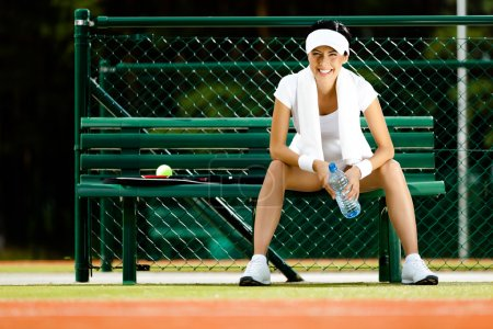 Tennis player rests at the bench
