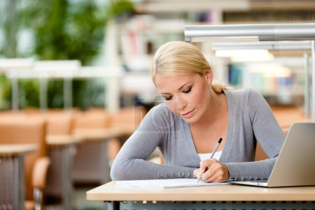 Photo for Female student working on the laptop sitting at the table. Process of learning - Royalty Free Image