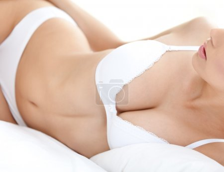 Body of a halfnaked woman in white bra