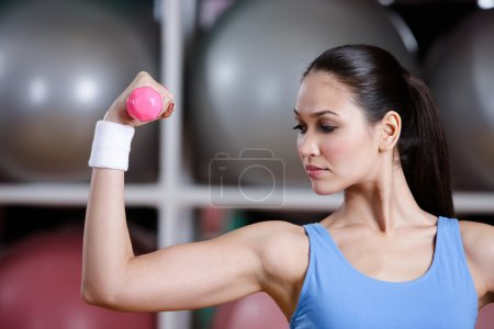 Young woman training with pink dumbbells