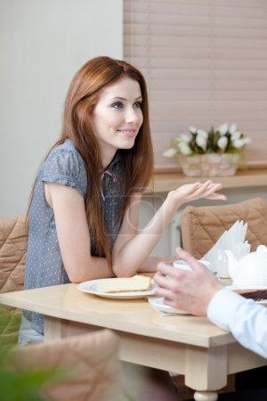 Photo pour Femme parle avec un homme assis à la table au café - image libre de droit