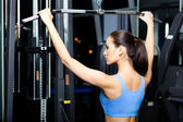 Athletic young woman works out on simulator