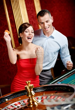 Happy couple playing roulette wins