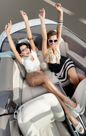 Top view of women in the cabriolet with their hands up