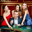 Man surrounded by women plays roulette at the casi...