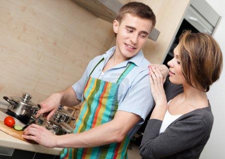 Photo pour Homme en tablier côtelettes légumes pour le dîner pour sa petite amie dans la cuisine moderne confortable - image libre de droit