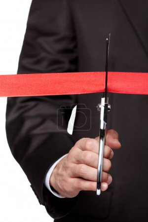 A businessman cutting a scarlet satin ribbon