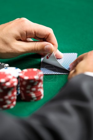 Photo for Gambler checking his cards. Risky entertainment of gambling - Royalty Free Image