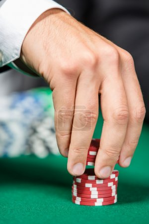 Poker player stakes the pile of poker chips
