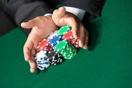 """Photo pour Le joueur joue """"all in"""" poussant ses jetons de poker vers l'avant. Divertissement risqué du jeu - image libre de droit"""