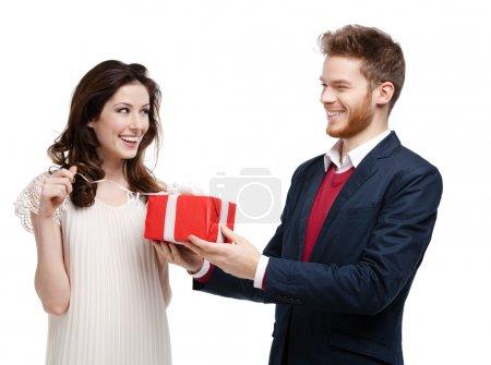 Photo pour L'homme donne présents emballés dans du papier rouge à sa petite amie, isolée sur blanc - image libre de droit