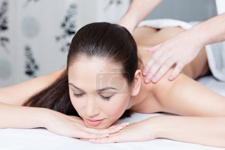 Young woman gets massage therapy