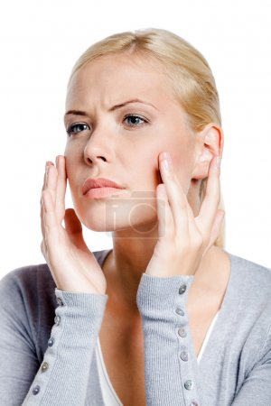 Woman examining her face and wrinkles that can appear, isolated on white