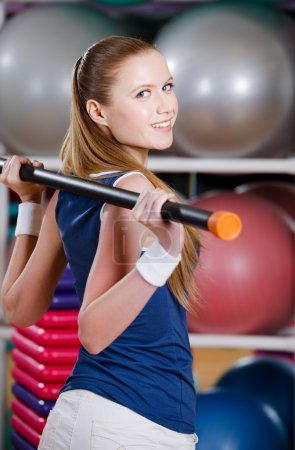 Sportive woman works out with gymnastic stick