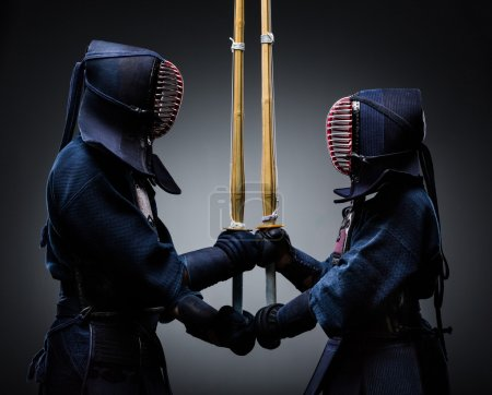 Two kendo fighters with shinai opposite each other...