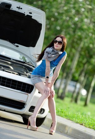 Photo for Woman sitting on the hood of the broken car and waiting for assistance - Royalty Free Image