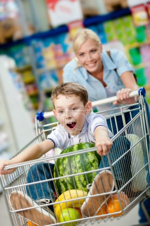 Little boy sits in the shopping trolley with watermelon