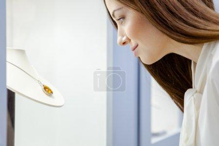 Photo pour Gros plan de la fille qui regarde collier saphir en vitrine à la bijouterie. Concept de richesse et de vie luxueuse - image libre de droit
