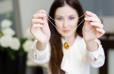Woman keeping necklace with yellow sapphire