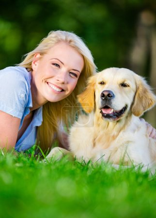 Close up of woman with golden retriever on the grass