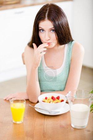 Mädchen isst gesundes Getreide mit Erdbeere