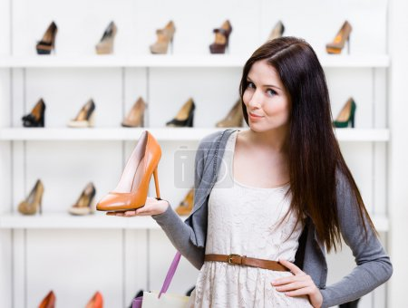 Photo for Half-length portrait of woman keeping brown leather shoe in shopping center - Royalty Free Image