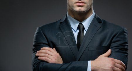 Photo for Partly viewed man wearing business suit and black tie with arms crossed - Royalty Free Image