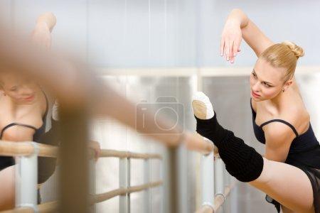 Pretty ballerina stretches herself near barre