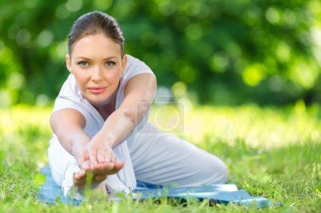 Photo pour Portrait de femme sportive s'étirant dans le parc - image libre de droit