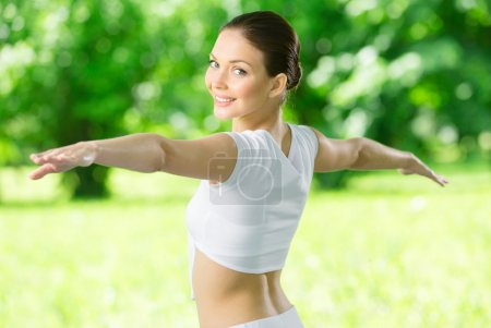 Portrait of exercising girl with outstretched arms