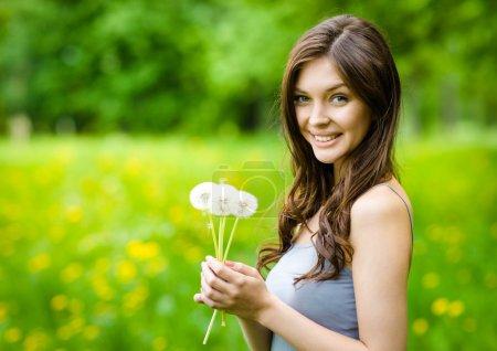 Photo pour Portrait de jeune femme mains pissenlits dans le parc. concept de la jeunesse et de beauté naturelle - image libre de droit