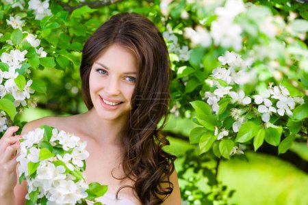 Photo for Portrait of beautiful woman near the blossomed tree in the park. Concept of youth and natural beauty - Royalty Free Image