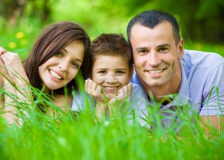 Dreiköpfige glückliche Familie liegt im Gras